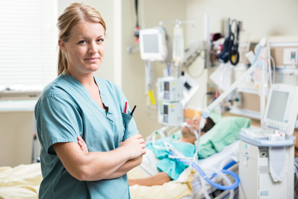 Portrait of confident nurse standing arms crossed with patient r