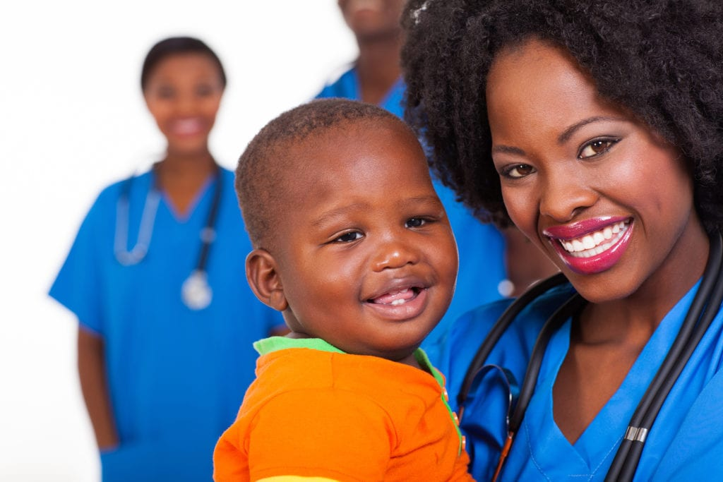 happy young african nurse carrying baby boy with colleagues on b